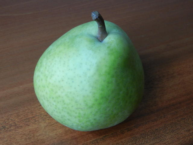 A green pear with an almost bluish tinge, on a wooden surface