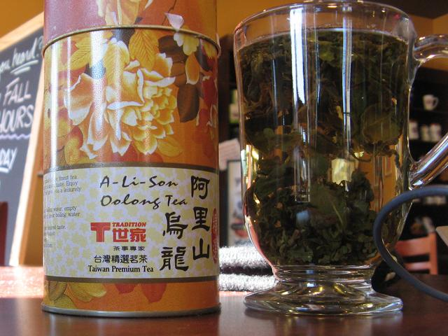 A canister of oolong tea, tradition brand, and a glass mug with loose-leaf tea brewing in it