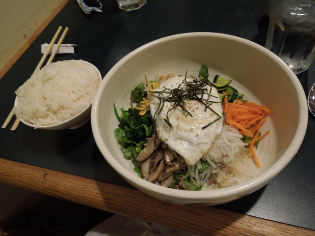 A bowl of bibimbap, assorted vegetables and egg, and rice on the side