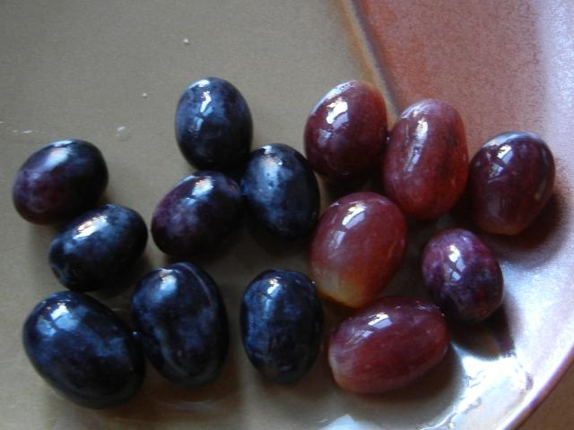 Whole black grapes on the left, whole red grapes on the right, on a brown ceramic plate