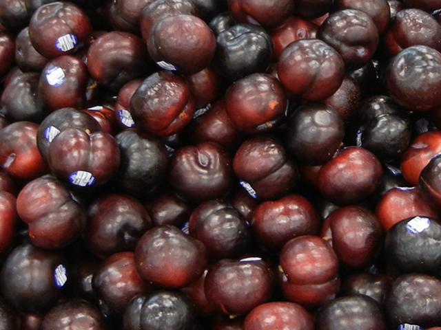 Black plums, a rich dark purple and red color, with shiny skin