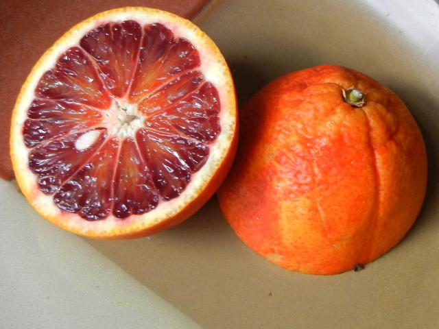 A blood orange sliced in half, showing a cross-section of the interior with a deep red hue, and one sliced seed, and the other half showing the skin with a reddish tinge