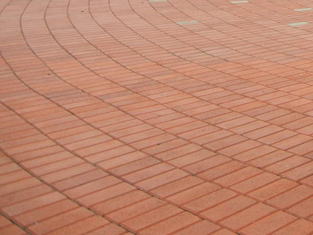 Red sidewalk bricks laid out in a circular pattern, radiating from a spot off the photo to the upper right