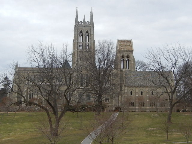 A stone cathedral in winter, surrounded by large greenish-tan lawns and bare trees