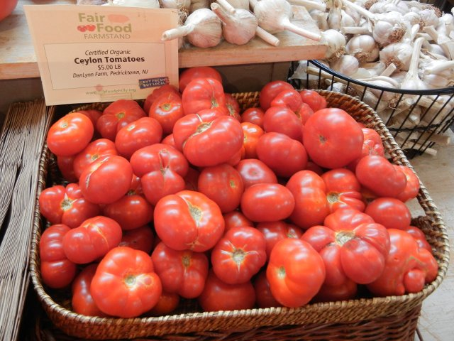 A basket of ceylon tomatoes, a bright red, round but somewhat flat variety of tomato