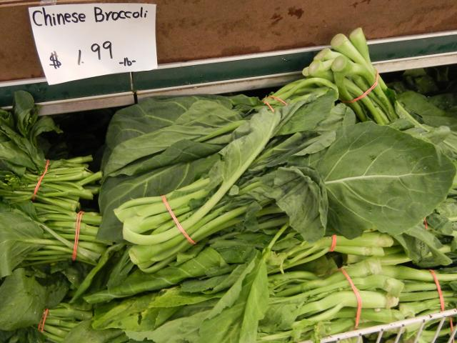 Raw chinese broccoli, a leafy green vegetable with long stalks, tied in bunches with rubber bands, with a sign