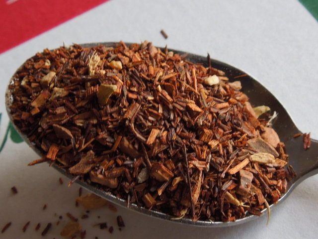 A spoon of spiced rooibos, showing mostly red rooibos leaf and stem with some spices