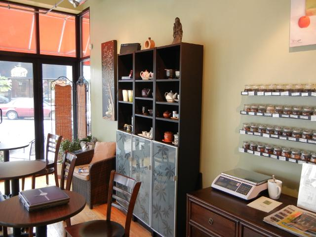 The wall in a tea shop, with small jars of tea, and shelves with teaware, and a scale