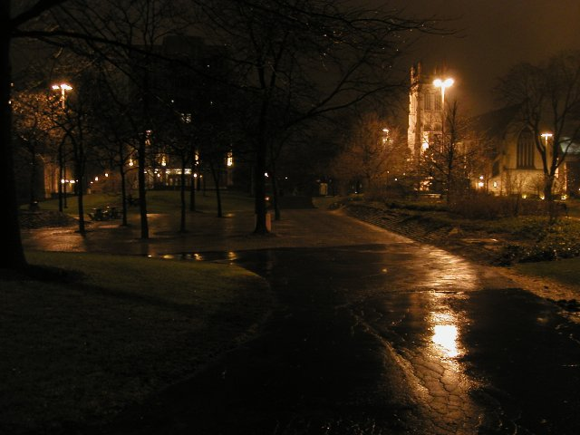 Dimly lit campus photo, with an asphalt walkway, wet from rain, some orange street lights, and a church tower visible in the background