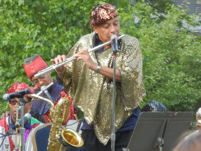 Photo of an older man with a gold sequined robe and a red sequined hat, playing flute in front of a microphone, with two musicians in similar, brightly colored outfits on the left, and trees in the background