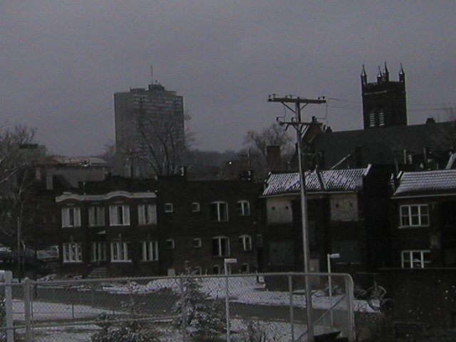 Three two-story apartment buildings, the middle one boarded up, with snow on the ground, and a high-rise building and a church in the background