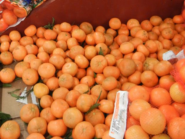 Whole, fresh Mandarin oranges, a small, flat, orange-shaped citrus fruit, with a few stems and leaves attached