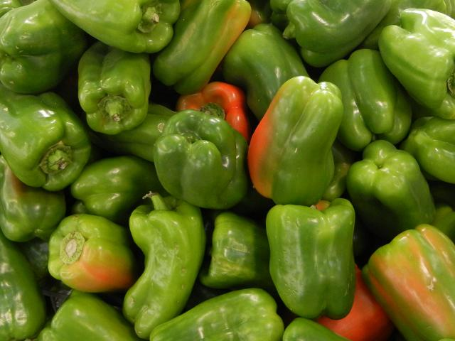 Many large green bell peppers with some red color on some