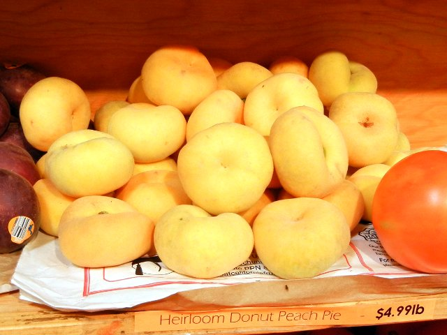 All yellow donut peaches on a shelf, with a sign reading Heirloom Donut Peach Pie, $4.99lb