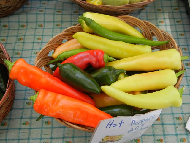 A basket of assorted hot peppers, orange, yellow, red, dark green and light green, and a sign reading: Hot peppers, 20 cents each