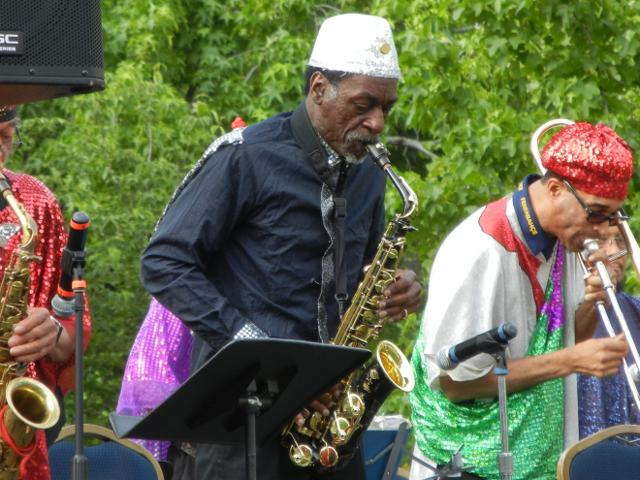 An older black man playing alto saxophone, with a white sequined fez, surrounded by a band of musicians in brightly colored, shiny outfits, with a music stand and microphone in the foreground trees in the background