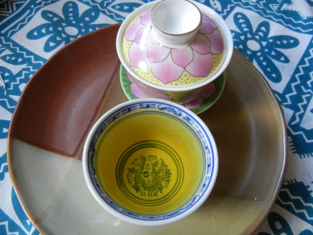 A gaiwan, a Chinese lidded bowl, closed, with a pink and yellow pattern on the lid, and a small teacup with a rich golden-yellow infusion in it