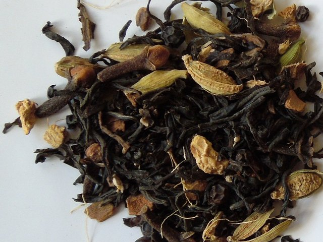 loose-leaf masala chai, showing black tea leaf, cardamom pods, clove, and other spices