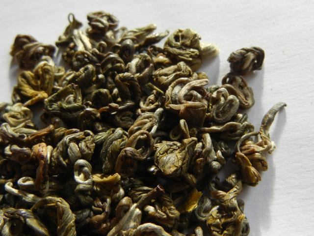 Loose-leaf green tea with tightly rolled shapes, somewhat spindly-looking, and golden and silvery green in color
