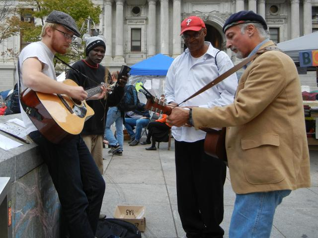 Three musicians, with two guitar players, and one man watching, at the Occupy Philly protest in front of city hall, Philadelphia