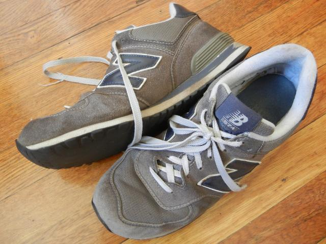 A relatively old pair of New Balance Classics 574 sneakers on a wooden floor