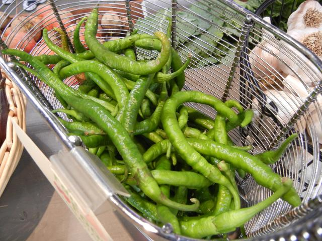 Organic cayenne peppers, long, narrow, green, slightly crinkly peppers, in a metal basket