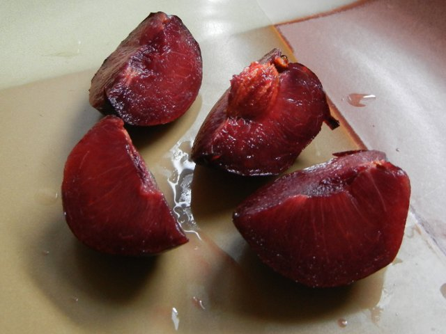 A sliced pomegranate pluot, a plum-like fruit showing dark purple flesh, on a brown ceramic plate