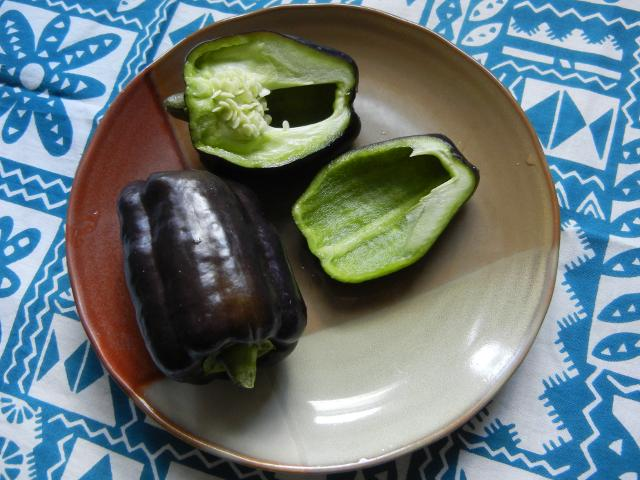 Two purple-black bell peppers, on a ceramic plate, one pepper sliced, showing bright green interior