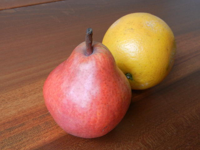 A red pear and a Valencia orange on a wooden surface