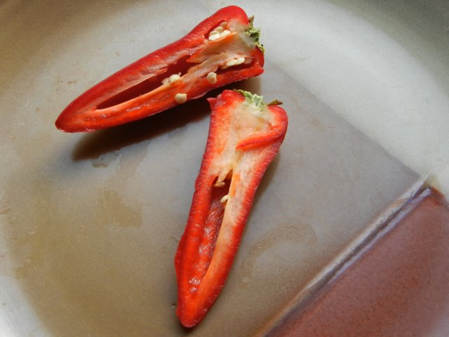 A sliced red fresno pepper, cut in half, showing the pepper interior, intense red color, green stem, straight conical shape, and a few seeds at the top, on a brown ceramic plate