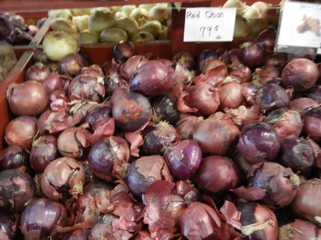 A bin of red onions, with a sign reading: red onion, 79 cents -lb-