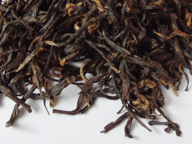 Loose-leaf black tea showing golden tips and a curved, twisted shape