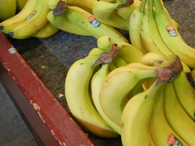 Bunches of ripe yellow bananas, bearing the Del Monte brand name