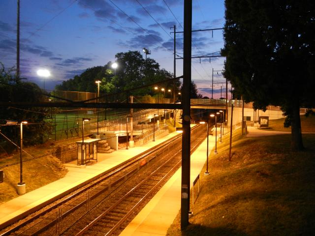 A train station just after dusk, showing tracks and a low platform, with an illuminated athletic field on the left, and a few lingering colors of sunset in the distance