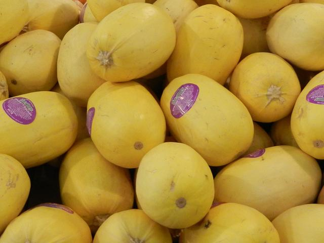 Big, oval-shaped, yellow squash, some with purple stickers on them