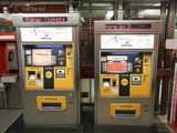 Two electronic PATCO ticket machines, with metal, yellow, and black surfaces and lots of color, a red PATCO station in the background