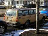 An old, beige volvo station wagon, with a boxy look, in good shape, with red hat linux and apple computer stickers on the rear window, sun reflecting off the rear window, snow on the ground, and a white house in the background