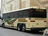A coach bus parked in a parking lot in a city, with BIEBER written on the side
