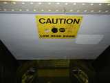 A sign on a low ceiling reading: caution, low head room, showing a picture of a person's head and a bump, with the person saying ouch