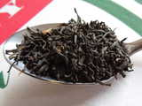 A spoon of loose-leaf black tea, showing large, dark intact leaves