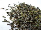 Fine tea leaves with a heterogenerous color, ranging from light green to brown, curly, some with fine hairs