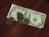 A dollar bill on a table, with four quarters on it, and one penny