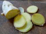 A ginger root and thin slices, on a cutting board