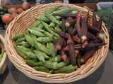 A basket containing fresh green okra pods on the left, and red okra pods on the right, with a few other vegetables around the edge of the photo