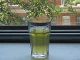 A glass of iced green tea, with no ice, on a windowsill with trees and a brick building in the background