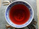 A small chinese teacup, on a hotplate, filled with a deep red liquid