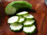 A small cucumber, seedless, with dark green wobbly edge, sliced and slices sitting on a dark wooden cutting board