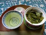 A gaiwan, a Chinese lidded bowl, open, filled with wet lemon verbena leaves, and a cup with a pale greenish-yellow liquid in it, the infusion of the lemon verbena
