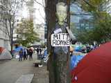 A picture of Frankenstein, labelled Mitt Romney, attached to a tree, surrounded by tents in a city