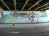 A mural painted on concrete under a bridge, depicting bicyclists in a bicycle race